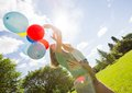 Mother and daughter holding balloons in park side view of colorful Royalty Free Stock Photo