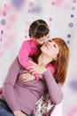 Mother and daughter kissing pink decoration Royalty Free Stock Images
