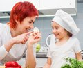 Mother and daughter in the kitchen with mushrooms Royalty Free Stock Photos