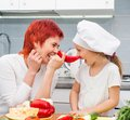 Mother and daughter in the kitchen with pepper Royalty Free Stock Images