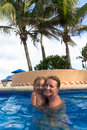 Mother and daughter laughing in the pool having great time swimming under palm trees Royalty Free Stock Photos