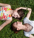 Mother with the daughter laying on a grass in park Stock Images