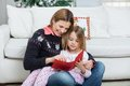 Mother and daughter with letter sitting at home during christmas Royalty Free Stock Images