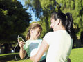 Mother and daughter listening to mp player in park sharing headphones smiling tilt Royalty Free Stock Photography