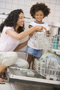 Mother And Daughter Loading Dishwasher Royalty Free Stock Photo