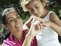 Mother and daughter looking at bug on hand smiling close up tilt Stock Photography