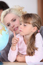 Mother and daughter looking at a globe light Royalty Free Stock Photos