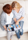 Mother and daughter looking photo book two women at home Stock Photo