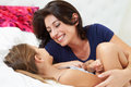 Mother and daughter lying in bed together smiling to each other Royalty Free Stock Photos