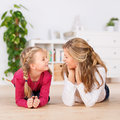 Mother and daughter lying comfortably on floor smiling little the in house Royalty Free Stock Images