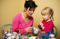 Mother and daughter making christmas decorations family scene of a young together Royalty Free Stock Photo