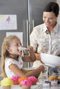 Mother and daughter making cupcakes happy with tasting cupcake batter in kitchen Royalty Free Stock Photos