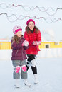 Mother and daughter mold snowballs at outdoor skating rink happy in winter Stock Photography