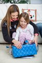 Mother and daughter opening christmas present at home Royalty Free Stock Photos