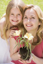 Mother and daughter outdoors holding flower Royalty Free Stock Photo