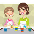 Mother daughter painting together colorful easter eggs holiday party Stock Photography