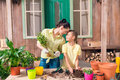Mother and daughter with plants and flowerpots standing at table