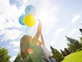 Mother and daughter playing with balloons in park helium summer Stock Image