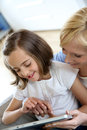 Mother and daughter playing with electronic tablet Royalty Free Stock Image