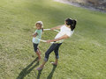 Mother and daughter playing with hula hoop on grass in park smiling side view elevated view Royalty Free Stock Image