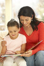 Mother and daughter playing reading book at home Royalty Free Stock Image