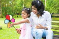 Mother and daughter playing windmill happy indian family outdoor activity candid portrait of at garden park Royalty Free Stock Image