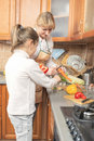 Mother and daughter preparing healthy organic food together in the kitchen vertical image composition Royalty Free Stock Images