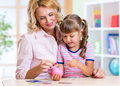 Mother and daughter putting coins into piggy bank Royalty Free Stock Photo