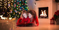 Mother and daughter read a book at fireplace on Christmas eve.