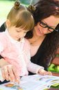Mother with daughter read a book in the park Stock Photography