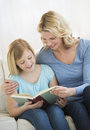 Mother and daughter reading book together at home happy on sofa Stock Image