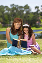 Mother and Daughter Reading Book Together Outside Royalty Free Stock Images