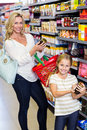 Mother and daughter reading nutritional values of products in supermarket Royalty Free Stock Photography