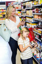 Mother and daughter reading nutritional values of products in supermarket Stock Photo