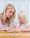 Mother and daughter reading together in the living room Stock Photos