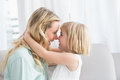 Mother and daughter rubbing noses on sofa Royalty Free Stock Photo