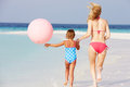 Mother and daughter running on beautiful beach with balloon having fun Stock Photo