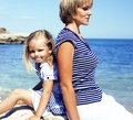 Mother with daughter at sea cost together, happy real family lif Royalty Free Stock Photo