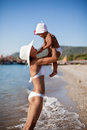 Mother and daughter at the seaside hold s her baby in arms staying in water Royalty Free Stock Image