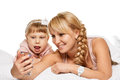 Mother daughter selfie and are happy together making with smartphone freetime in bed Stock Photography