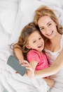 Mother daughter selfie in white bed and are happy together making with smartphone freetime Royalty Free Stock Image