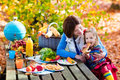 Mother and daughter set table for picnic in autumn Royalty Free Stock Photo