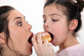 Mother and daughter sharing doughnut a dough nut Royalty Free Stock Photos