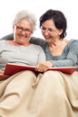 Mother and daughter sharing memories photo album family of two women senior adult sitting on sofa isolated on white background Stock Images