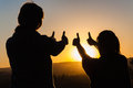 Mother daughter silhouetted thumbs up contrasted by sunset giving a for the day Stock Images