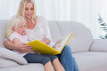 Mother and daughter sitting on couch reading a book Stock Photo