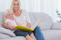 Mother and daughter sitting on couch reading a book looking at camera Royalty Free Stock Image