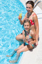 Mother and daughter sitting on edge of pool with drink smiling the the a in hand Stock Photos