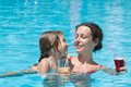 Mother and daughter sitting on edge of pool with drink smiling the the a in hand Stock Image