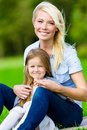 Mother and daughter sitting on the grass embrace each other leisure time of happy family Royalty Free Stock Photos